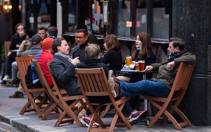Drinkers outside a pub in Soho, London, on the first day after the city was put into Tier 2 restrictions to curb the spread of coronavirus. PA Photo. Picture date: Saturday October 17, 2020. Under Tier 2 restrictions the rule of six applies for socialising outside, and pubs, bars and restaurants have a 10pm curfew. - Dominic Lipinski/PA Wire