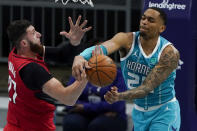 Portland Trail Blazers center Jusuf Nurkic vies for a loose ball with Charlotte Hornets forward P.J. Washington during the first half in an NBA basketball game on Sunday, April 18, 2021, in Charlotte, N.C. (AP Photo/Chris Carlson)