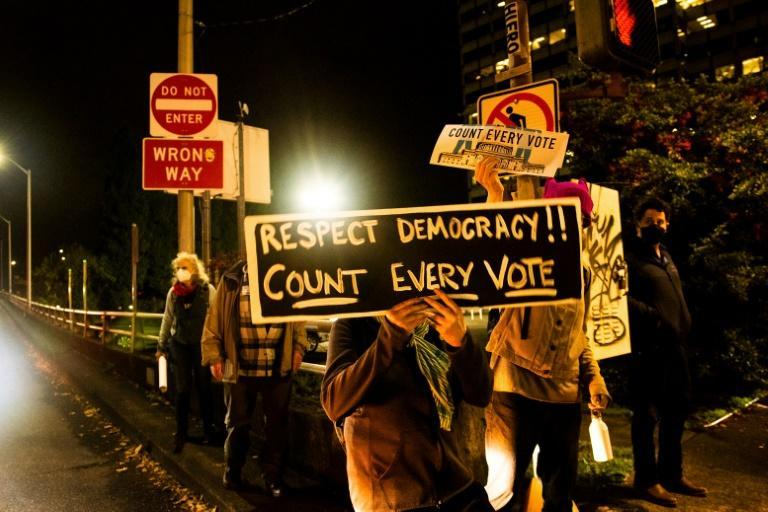 A protester holds a sign reading 'Respect democracy! Count every vote' during a demonstration in Portland, Oregon