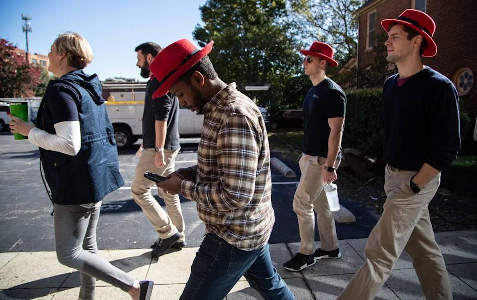 Red Hat employees walk back to their Raleigh headquarters after a meeting at the Duke Energy Center for the Performing Arts Monday, Oct. 29, 2018.