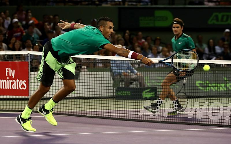 Nick Kyrgios stretches for a shot against Roger Federer - Credit: Getty