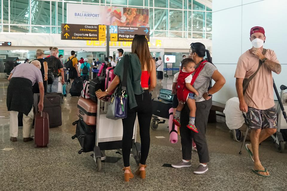 Australians and their families queue at the entrance to the international terminal at Ngurah Rai airport near Denpasar on the tourist island of Bali. Source: Getty