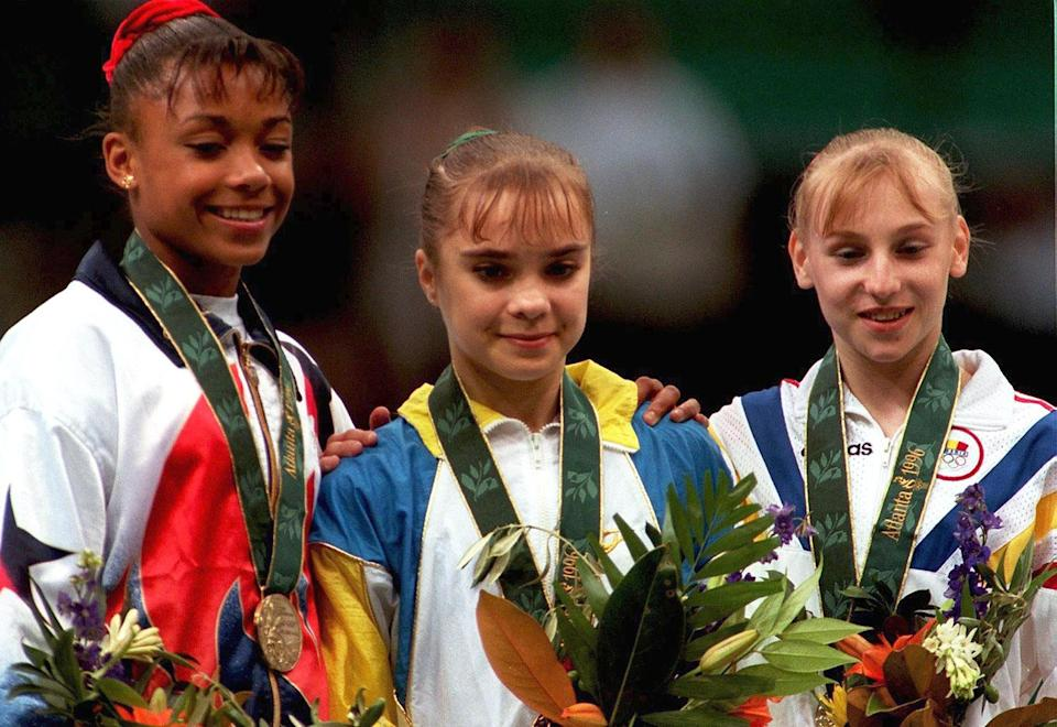 <p>Gold medalist Lilia Podkopayeva pf Ukraine on the medal podium at the 1996 Atlanta Olympics with silver medalist Simona Amânar and bronze medalist Dominique Dawes. (Photo by Bongarts/Getty Images) </p>