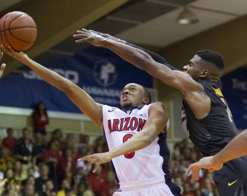 Arizona guard Parker Jackson-Cartwright, left, ducks under Missouri guard Keith Shamburger, right, and shoots a layup in the first half of an NCAA college basketball game at the Maui Invitational on Monday, Nov. 24, 2014, in Lahaina, Hawaii. (AP Photo/Eugene Tanner)