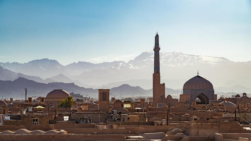 Jameh Mosque and snowcapped mountains in Yazd, Iran. Credit: Jean-Philippe Tournut. Moment. Getty Images