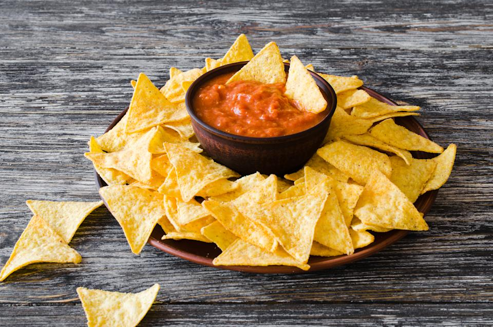Nachos corn chips with spicy tomato sauce. Mexican food concept. Yellow corn totopos chips with salsa sauce. Top view.