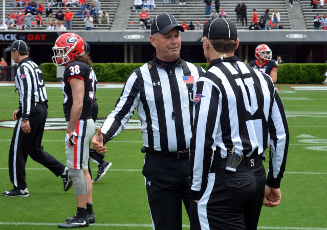 In this April 20, 2019 photo, Tom Quick talks with a colleague during Georgia's spring NCAA college football game in Athens, Ga. Theyre jobs have never been more difficult. Those who do it face relentless, often uninformed criticism, and attacks on their credibility. (Gary McGriff via AP)