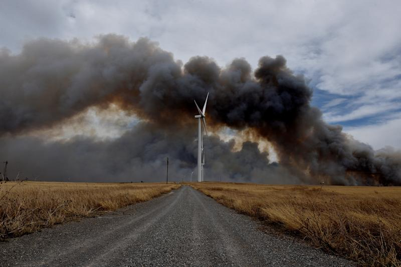 The Rhea fire burns in the distance behind a wind farm near Seiling, Oklahoma. (Nick Oxford / Reuters)