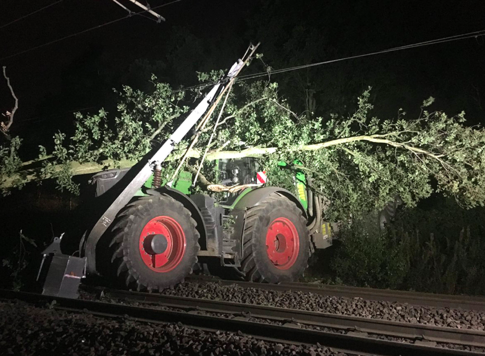 <em>A large uprooted tree laid on top of the tractor (PA)</em>