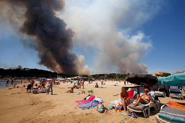 <p>Smoke fills the sky above a burning hillside as tourists relax on the beach in Bormes-les-Mimosas, in the Var department, France, July 26, 2017. (Jean-Paul Pelissier/Reuters) </p>