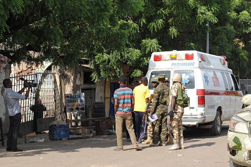 Emergency services and soldiers gather at the scene of a suicide bomb attack on a market in Maiduguri, after two girls approximately seven or eight years old blew themselves, killing themselves and wounding at least 17 others (AFP Photo/STR)