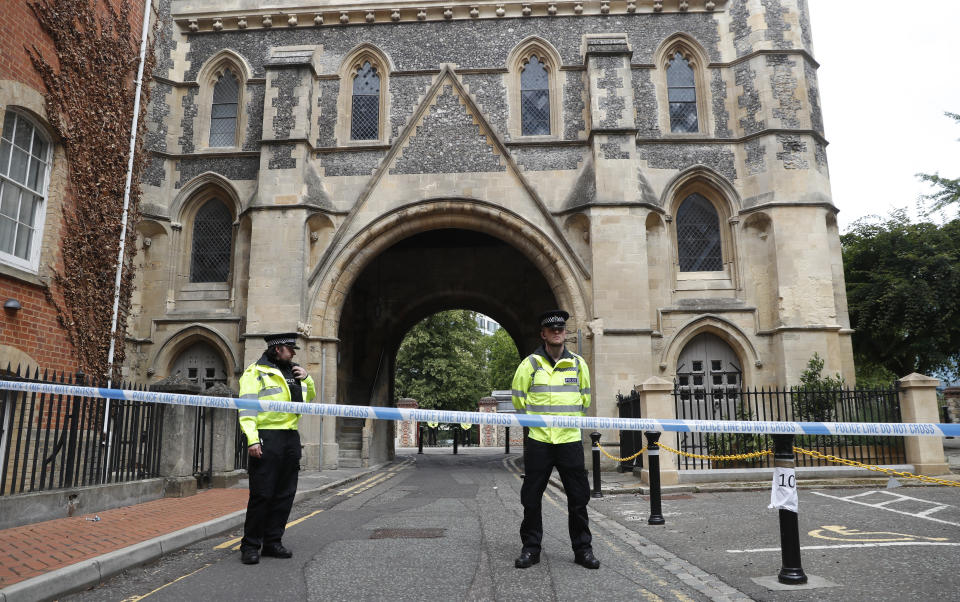Police stand guard at the Abbey gateway of Forbury Gardens, a day after a multiple stabbing attack in the gardens in Reading, England, Sunday June 21, 2020. British police say they are treating a stabbing rampage in a park that killed three people as a terrorist attack. Dean Haydon, the U.K.'s coordinator of counterterrorism policing, said counterterror detectives were taking over the investigation into the attack in the town of Reading, west of London. (AP Photo/Alastair Grant)