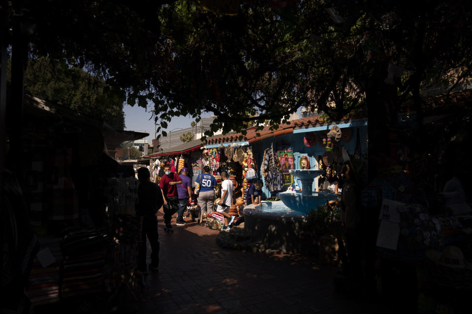 People shop on Olvera Street in Los Angeles, Friday, June 4, 2021. Olvera Street has long been a thriving tourist destination and a symbol of the state's early ties to Mexico. The location of where settlers established a farming community in 1781 as El Pueblo de Los Angeles, its historic buildings were restored and rebuilt as a traditional Mexican marketplace in 1930s. As Latinos in California have experienced disproportionately worse outcomes from COVID-19, so too has Olvera Street. (AP Photo/Jae C. Hong)