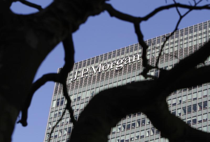 A sign on the Canary Wharf offices of JP Morgan is seen through the branches of a tree in London