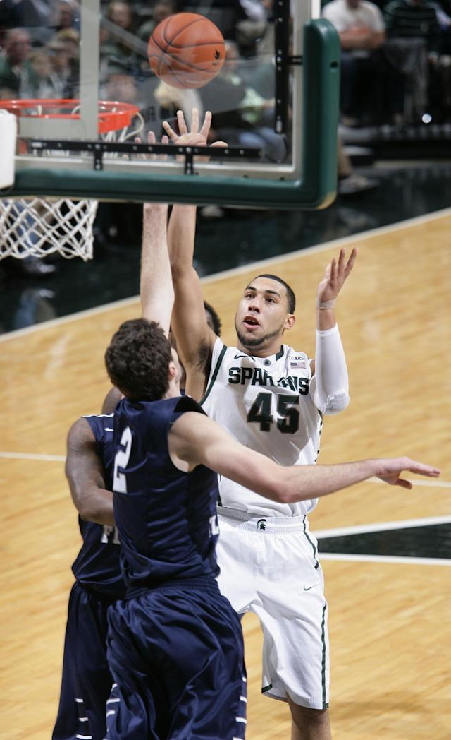 Michigan State's Denzel Valentine (45) shoots against North Florida's Beau Beech during the first half of an NCAA college basketball game, Tuesday, Dec. 17, 2013, in East Lansing, Mich. Michigan State won 78-48. (AP Photo/Al Goldis)