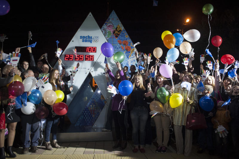 Volunteers jubilate as the countdown clock shows 100 days left until the start of 2014 Winter Olympic Games at a square at the Black Sea resort of Sochi, southern Russia, Tuesday, Oct. 29, 2013. Russia is spending more than $50 billion on the Olympics, President Vladimir Putin's pet project. Putin said the Olympic construction is largely complete, with only some details remaining to be completed. (AP Photo/Lesya Polyakova)