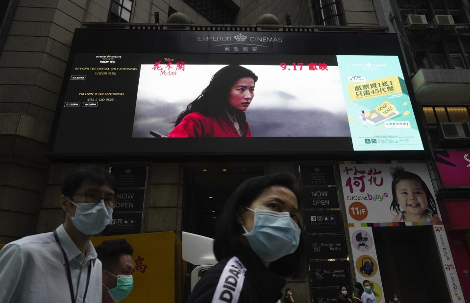 """People walk past a huge TV screen showing movie """"Mulan"""" at a downtown street in Hong Kong Thursday, Sept. 17, 2020. The remake of """"Mulan"""" struck all the right chords to be a hit in the key Chinese market. Disney cast beloved actresses Liu Yifei as Mulan and removed a popular dragon sidekick in the original to cater to Chinese tastes. (AP Photo/Vincent Yu)"""