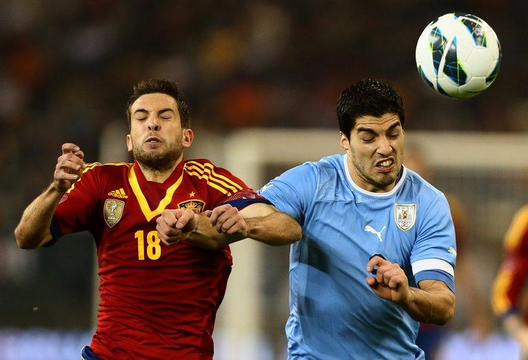 Uruguay's Luis Suarez (R) holds off Spain's Jordi Alba during the friendly in Doha on February 6, 2013