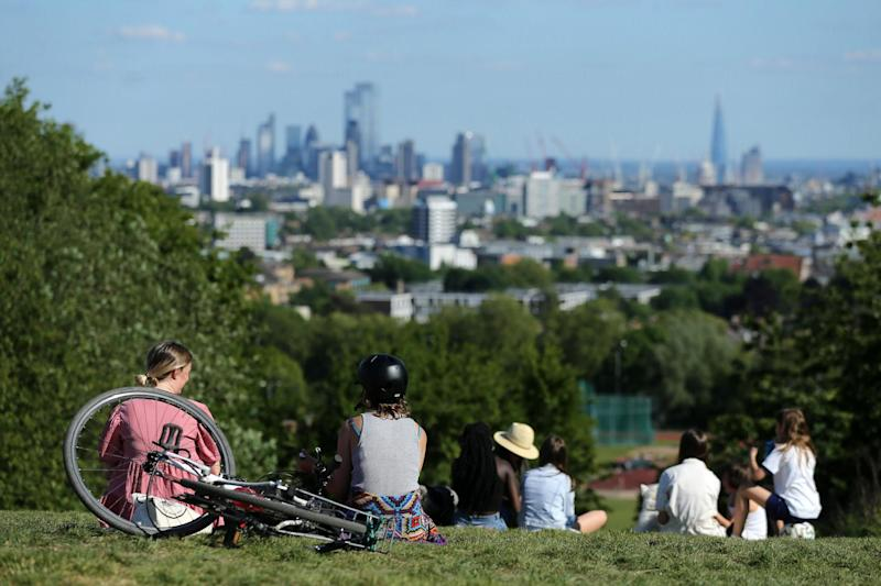 People walk in the afternoon sunshine on Hampstead Heath, north London: AFP via Getty Images