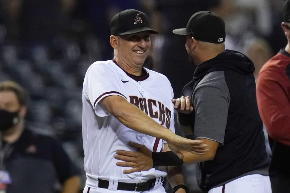 Arizona Diamondbacks manager Torey Lovullo, left, smiles as he celebrates a win against the Milwaukee Brewers with Diamondbacks' David Peralta, right, after the final out of the ninth inning of a baseball game Monday, June 21, 2021, in Phoenix. The Diamondbacks defeated the Brewers 5-1. (AP Photo/Ross D. Franklin)