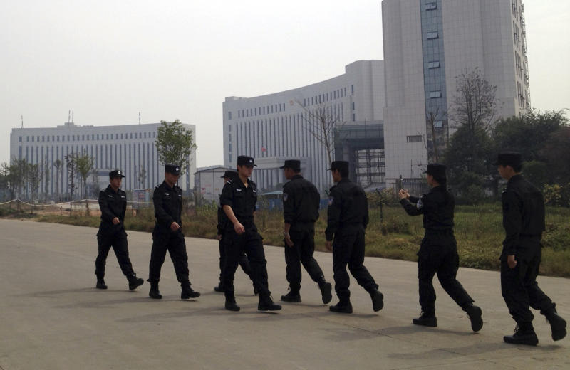 Chinese police officers march past the courthouse where a trial of Chinese activists is under way in Xinyu city in eastern China's Jiangxi province on Monday, Oct. 28, 2013. Three Chinese activists from a group that urges fellow citizens to embrace their constitutional rights stood trial Monday in the Xinyu district court in a closely watched case that underscores the Communist Party's intolerance of organized political challenge - no matter how small.(AP Photo/Aritz Parra)