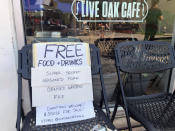 The Oak Street Café in New Orleans offers free food to passers-by on Thursday, Sept. 2, 2021, as the city recovers from damage and power outages caused by Hurricane Ida. (AP Photo/Kevin McGill)