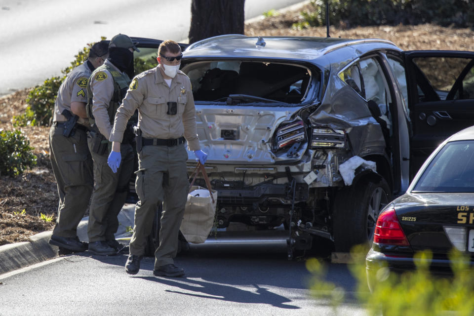 Los Angeles County Sheriff deputies gather evidence from Tiger Woods' car after a crash.