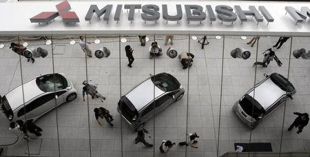 Mitsubishi Motors Corp's the i-MiEV electric vehicles are reflected on an external wall in Tokyo