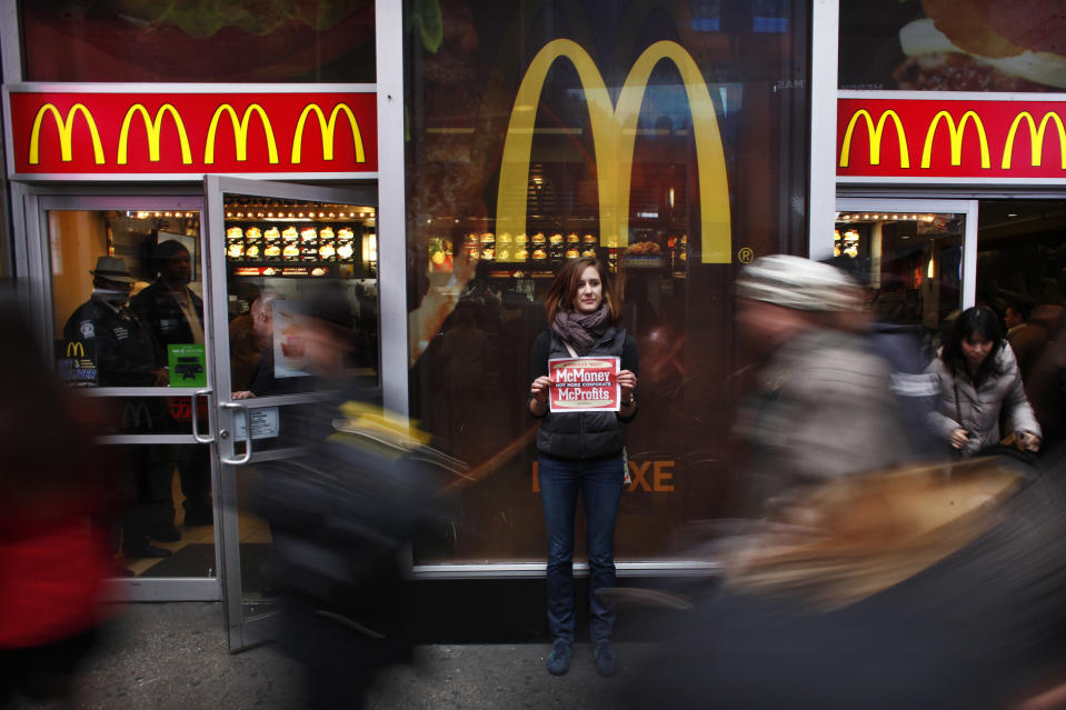 "A member of 'MoveOn' holds up a poster during a protest in front of McDonald's restaurant in Times Square, New York, December 4, 2013. MoveOn members will be protesting at McDonald's locations in five cities - Seattle, San Francisco, New York, Los Angeles, and Chicago, and delivering a petition started by ""Low Pay is Not Okay"". The petition, which is addressed to McDonald's, Burger King, Taco Bell, KFC, Pizza Hut, Domino's, Papa John's, and Subway, and has the support of nearly 50,000 MoveOn members, demands a $15/hour living wage for all fast food workers. REUTERS/Eduardo Munoz (UNITED STATES - Tags: CIVIL UNREST FOOD SOCIETY TPX IMAGES OF THE DAY)"