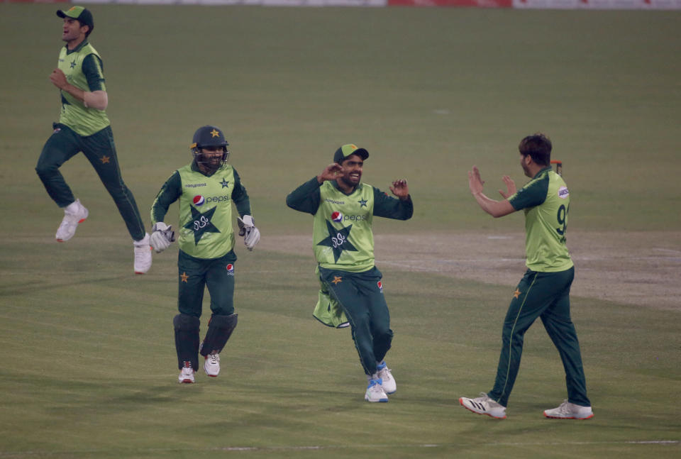 Pakistan's Usman Qadir, right, celebrates with teammates Babar Azam, center, and Mohammad Rizwan after taking the wicket of South Africa's Andile Phehlukwayo during the 3rd Twenty20 cricket match between Pakistan and South Africa at the Gaddafi Stadium, in Lahore, Pakistan, Sunday, Feb. 14, 2021. (AP Photo/K.M. Chaudary)
