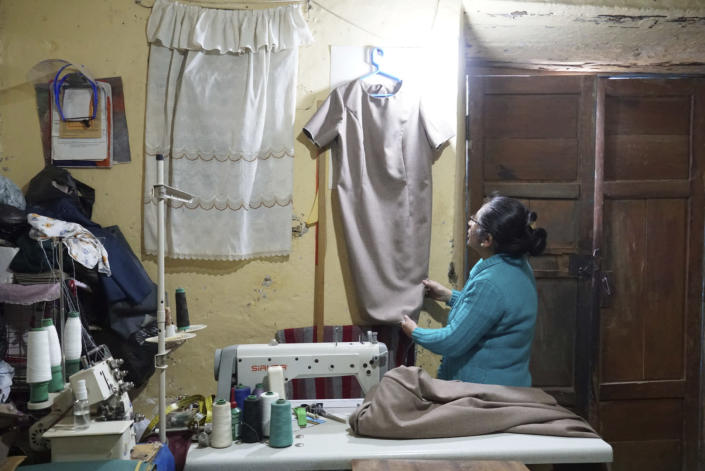 Seamstress Lupe de la Cruz, 55, checks one of the two dresses she has made for Peru's future first lady, Lilia Paredes, in her workshop where she lives with her 86-year-old mother and her dog Bobby, near Chugur, Peru, Thursday, July 22, 2021. Paredes' husband, leftist Pedro Castillo catapulted from unknown to president-elect with the support of the country's poor and rural citizens, many of whom identify with the struggles the teacher has faced. (AP Photo/Franklin Briceno)