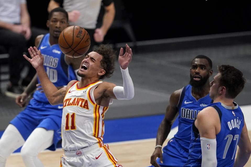 Atlanta Hawks' Trae Young is fouled going to the basket between Dallas Mavericks' Dorian Finney-Smith, Tim Hardaway Jr. and Luka Doncic during their game in Dallas on Feb. 10, 2021. (AP Photo/Tony Gutierrez)
