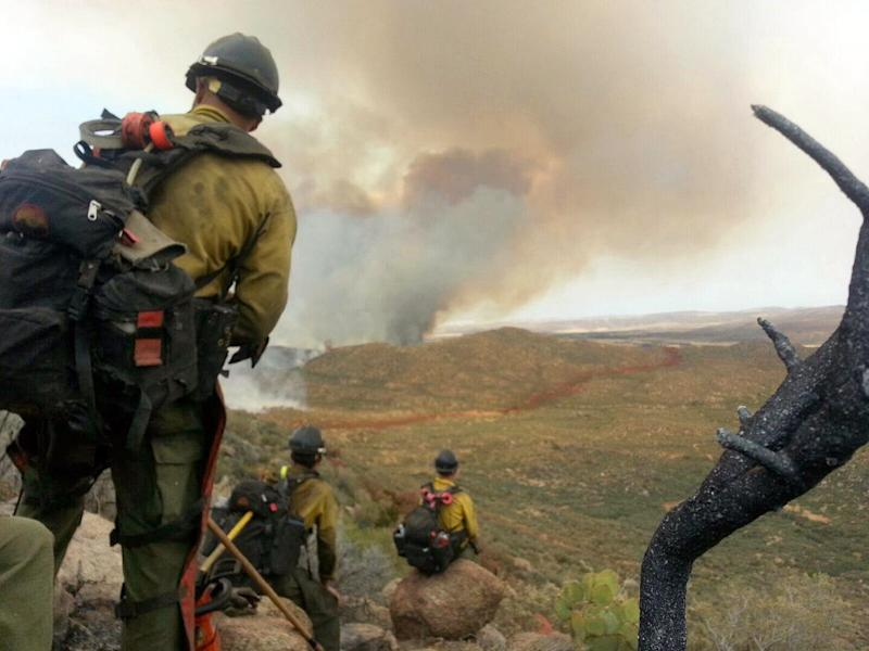 "In this photo shot by firefighter Andrew Ashcraft, members of the Granite Mountain Hotshots watch a growing wildfire that later swept over and killed the crew of 19 firefighters near Yarnell, Ariz., Sunday, June 30, 2013. Ashcraft texted the photo to his wife, Juliann, but died later that day battling the out-of-control blaze. The 29-year-old father of four added the message, ""This is my lunch spot...too bad lunch was an MRE."" (AP Photo/Courtesy of Juliann Ashcraft)"