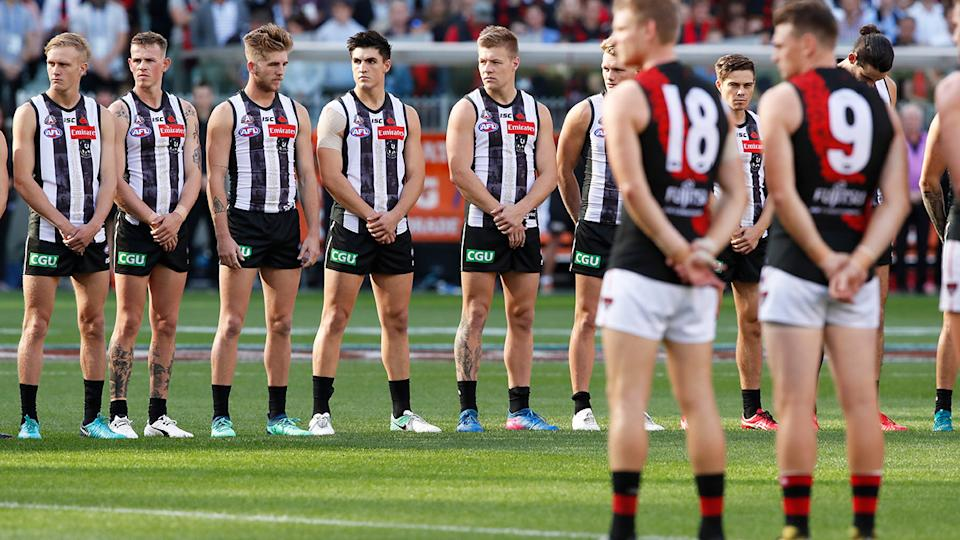 Collingwood and Essendon players, pictured here lining up before the Anzac Day game.
