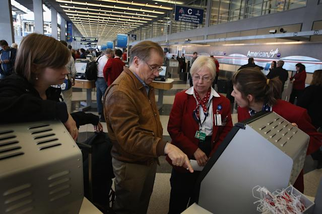 CHICAGO, IL - APRIL 16: American Airlines passengers Jim Frederick (C) and his daughter Lily (L) get help at O'Hare Airport trying to reschedule a flight home to Boston on April 16, 2013 in Chicago, Illinois. Thousands of American Airlines travelers became stranded today when the airline was forced to ground all its flights after a nationwide problem with its computer systems. (Photo by Scott Olson/Getty Images)