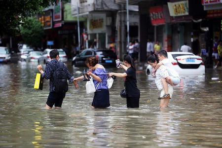 People walk through a flooded street as Typhoon Hato hits Dongguan, Guangdong province, China.    REUTERS/Stringer