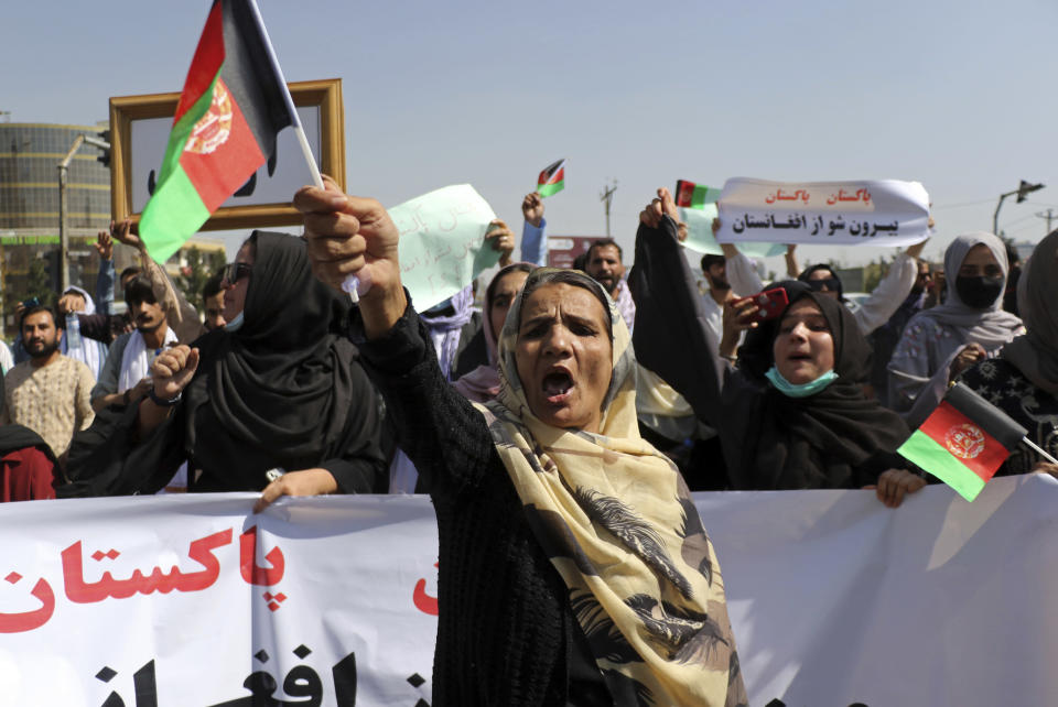 """Afghan women shout slogans and wave Afghan national flags during an anti-Pakistan demonstration, near the Pakistan embassy in Kabul, Afghanistan, Tuesday, Sept. 7, 2021. Sign in Persian at right reads, """"Pakistan Pakistan Get out from Afghanistan."""" (AP Photo/Wali Sabawoon)"""