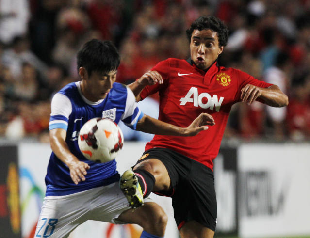 Manchester United's Fabio Da Silva, right, fights for the ball with Kitchee's Xu Deshuai during the friendly match between Manchester United and Kitchee SC in the Hong Kong Stadium, Monday, July 29, 2013. (AP Photo/Kin Cheung)