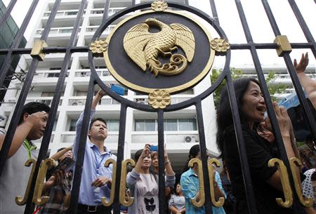 Thailand's Finance Ministry officers stand behind the ministry's gate while anti-government protesters rally outside in central Bangkok