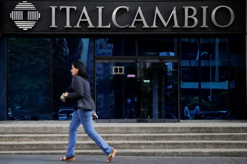 A woman walks past a branch of Italcambio currency exchange in Caracas