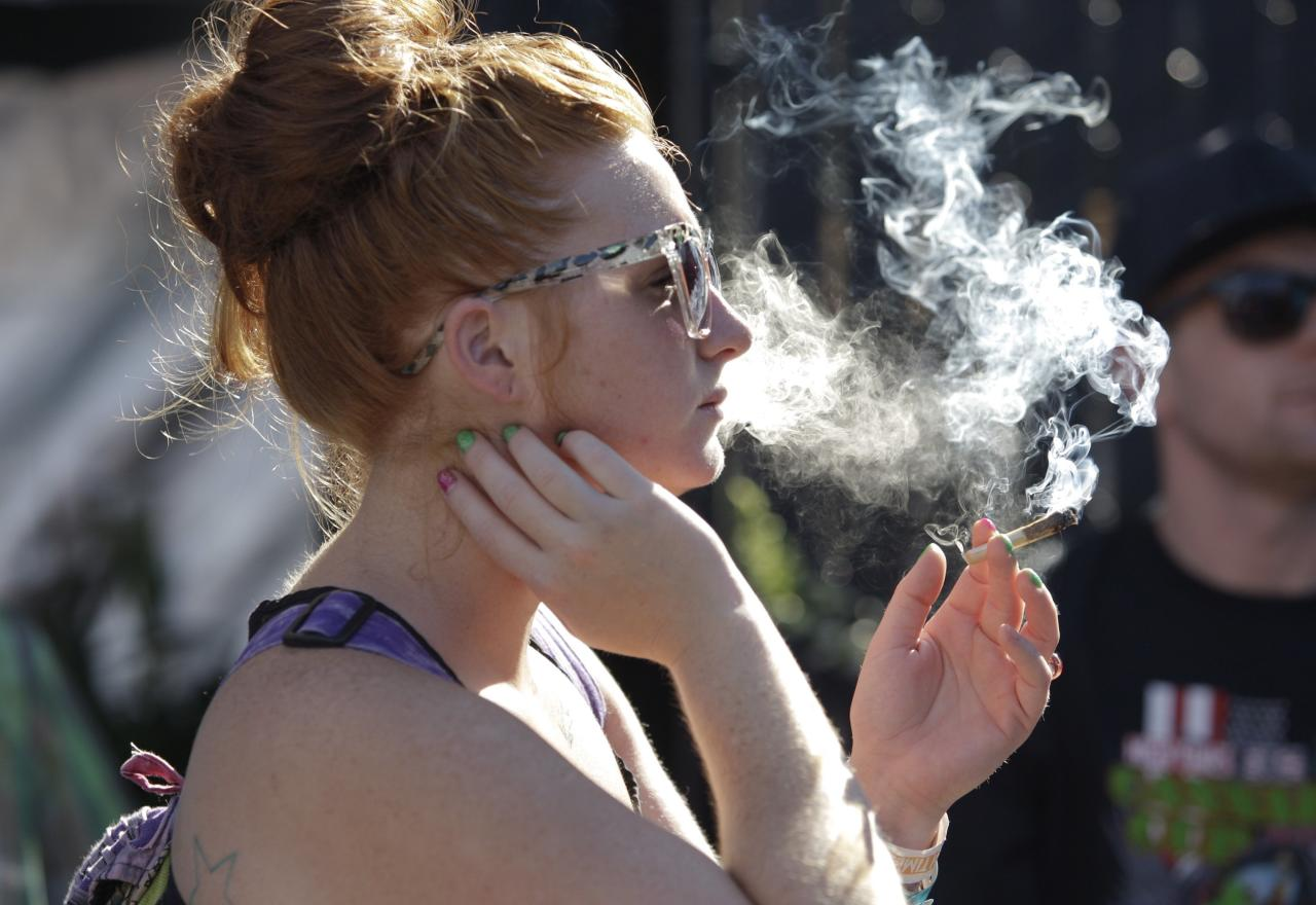 A woman smokes a joint at the High Times U.S. Cannabis Cup in Seattle, Washington September 8, 2013. Washington state was one of the first states to legalize marijuana for recreational use after approving separate ballot initiatives last year, even as the drug remains illegal under federal law. The Cup features exhibitions as well as a marijuana growing competition. REUTERS/Jason Redmond (UNITED STATES - Tags: DRUGS SOCIETY)
