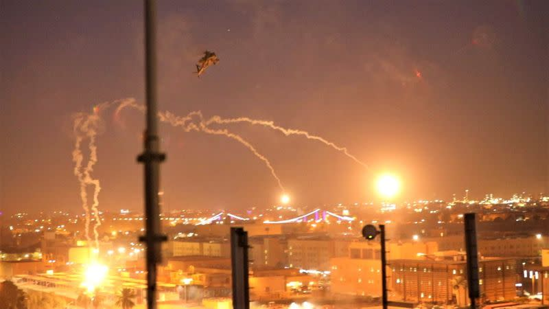 U.S. Army Apache helicopters launch flares as they conduct overflights of the U.S. Embassy in Baghdad