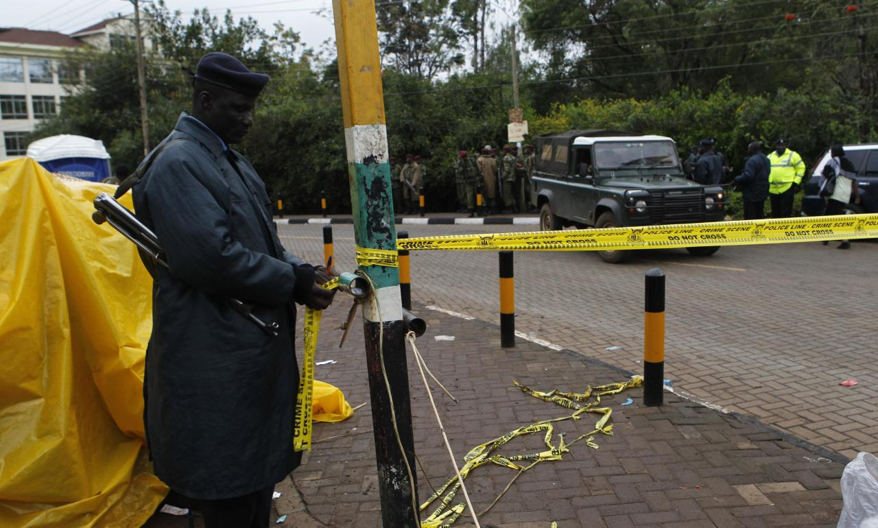 A Kenyan policeman secures the road past the Westgate Shopping Centre in the capital Nairobi, September 23, 2013. Heavy and sustained gunfire was heard from the Kenyan shopping mall where at least 68 people were killed in an attack by the Somali al Shabaab group, suggesting a possible assault by Kenyan security forces, a Reuters witness at the scene said. REUTERS/Thomas Mukoya (KENYA - Tags: SOCIETY CIVIL UNREST CRIME LAW)