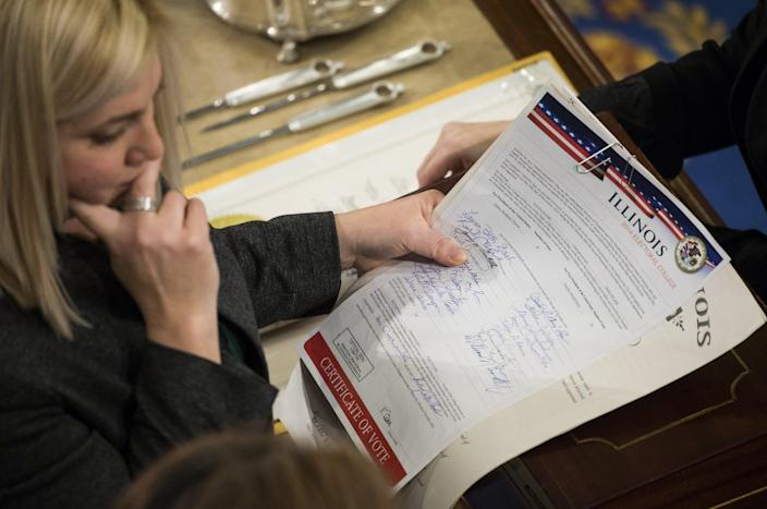 "<span class=""caption"">Staff of the House of Representatives review Illinois' Electoral College vote report in January 2017.</span> <span class=""attribution""><a class=""link rapid-noclick-resp"" href=""https://www.gettyimages.com/detail/news-photo/house-clerk-staff-verify-the-official-electoral-college-news-photo/631100318"" rel=""nofollow noopener"" target=""_blank"" data-ylk=""slk:Samuel Corum/Anadolu Agency/Getty Images"">Samuel Corum/Anadolu Agency/Getty Images</a></span>"
