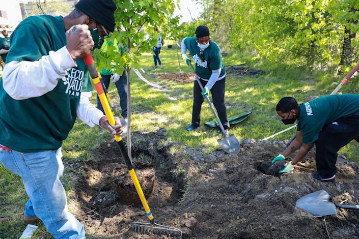 Volunteers plant trees during the kickoff event for Second Nature Brands' worldwide initiative to plant 1 million trees by planting over a dozen at Detroit's Black Bottom Park on May 14. The initiative is a partnership with nonprofit organizations ReLeaf Michigan, One Tree Planted and Vanguard Community Development.