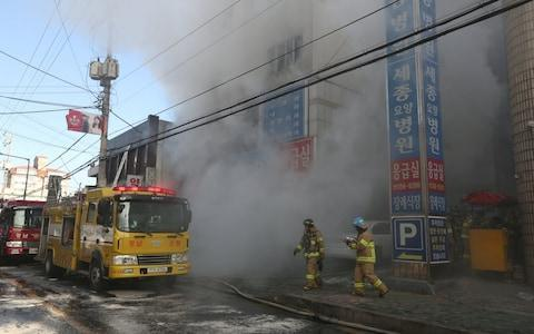 """A huge fire tore through a South Korean hospital on Friday killing at least 37 people, the government said, in the country's worst blaze for a decade. Around 130 others were hurt in the fire, which comes just weeks before thousands of athletes and foreign visitors are expected in the country for the Winter Olympics. While South Korea has risen to become the world's 11th-largest economy, some of its infrastructure was built rapidly and it has a history of preventable disasters. It was the country's second major blaze in a month, and officials admitted there was no sprinkler system installed at the hospital. Videos posted on social media showed a patient hanging on to a rope dangling from a helicopter above the hospital in Miryang, in the far south, and another crawling out of a window to climb down a ladder. The death toll rose rapidly throughout the morning as some of those initially pulled from the blaze succumbed to their injuries. At one point the presidential Blue House put it at 41, before authorities lowered it to 37, blaming double-counting. Firefighters try to put out a fire at a hospital building engulfed by heavy grey smoke in Miryang Credit: AFP Three of the dead were medical staff, officials said. """"Two nurses said they had seen fire suddenly erupting in the emergency room,"""" said fire chief Choi Man-Woo. The six-storey structure housed a nursing home as well as the Sejong Hospital, and around 200 people were inside when the fire broke out according to police. All the dead were in the hospital, Choi said. Video footage and pictures showed the building engulfed by thick, dark smoke and surrounded by multiple fire trucks. Survivors were brought out wrapped in blankets, and firefighters picked their way through the blackened shell of the building after the blaze was extinguished. Jang Yeong-Jae, a surviving patient, said he was on the second floor when nurses screamed """"Fire!"""" in the hallway and urged people to leave through the emergency exits. """"But when I op"""