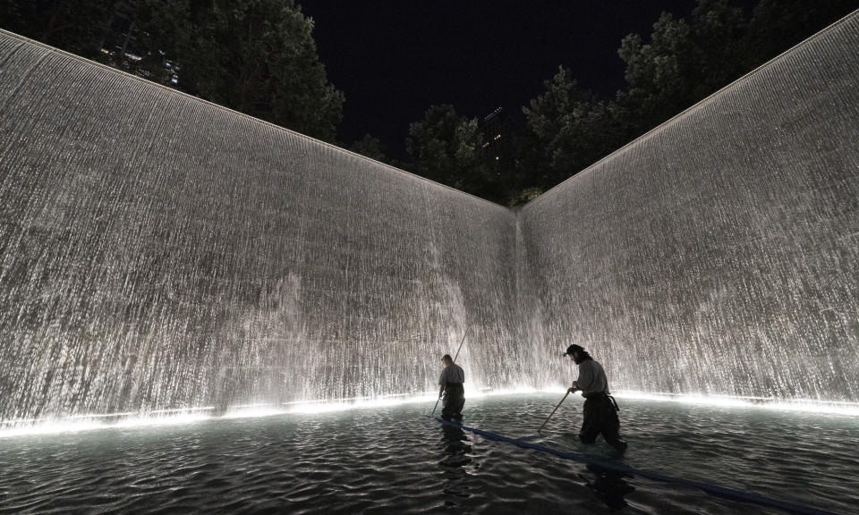 """James Maroon, left, cleans the bottom of the south pool of the 9/11 Memorial with a vacuum, Wednesday, Aug. 4, 2021 in New York. On Sept. 11, 2001 he was going to work at the New York Mercantile Exchange, just west of the twin towers. """"I was getting ready to cross the Westside Highway when the first plane hit and people were running up behind me,"""" he said. """"I thought a truck or something hit the walkway. I got out, looked up and the first plane was in the building. I thought it was just a small commuter plane because you didn't see a plane, just a hole. I ended going into work and then the second plane hit. I couldn't figure out where to go. Pretty much everything was closed off. I hooked up with a guy I worked with and we started walking up the Westside Highway and I looked back and the tower collapsed. Unbelievable."""" (AP Photo/Mark Lennihan)"""
