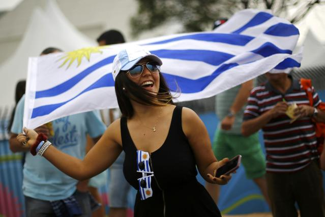 A supporter of Uruguay's national soccer team holds a flag during the team's final practice session at the Corinthians arena in Sao Paulo, one day before the match of the soccer World Cup between Uruguay and England, June 18, 2014. REUTERS/Ivan Alvarado (BRAZIL - Tags: SOCCER SPORT WORLD CUP)
