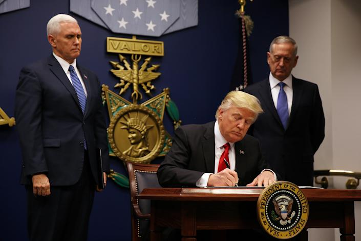 President Trump signs a travel ban executive order at the Pentagon as Vice President Mike Pence, left, and former Defense Secretary James Mattis look on, Jan. 27, 2017. (Carlos Barria/Reuters)