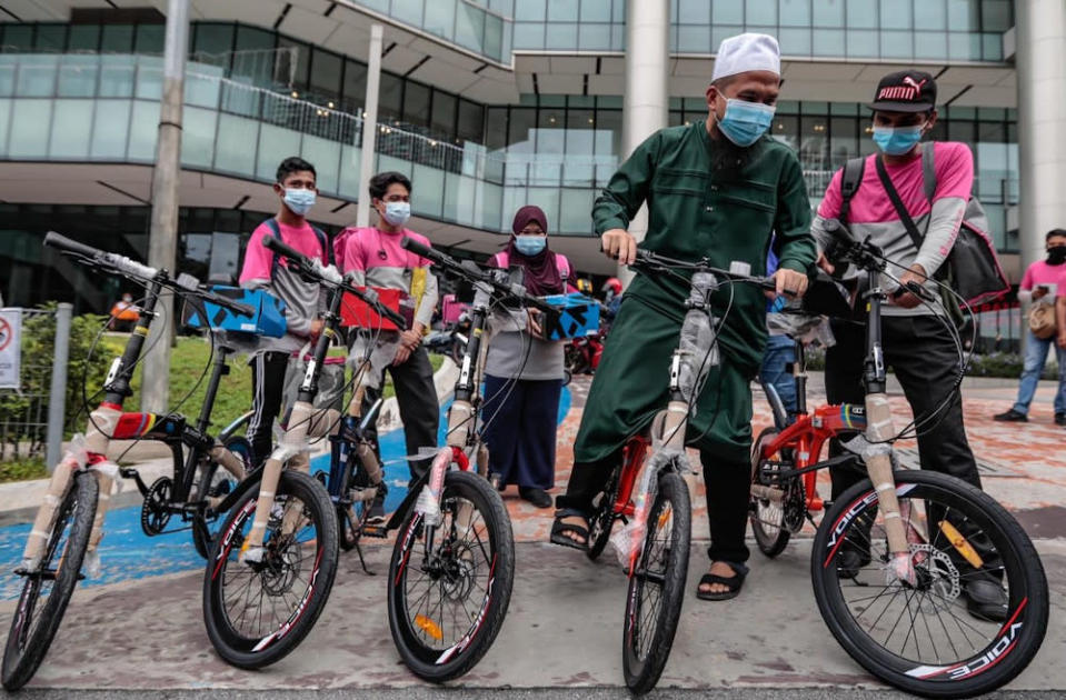 Ustaz Ebit Lew (in green) presenting the lightweight bicycles to help the delivery walkers with their food orders around Kuala Lumpur. — Picture via Facebook/EbitLew